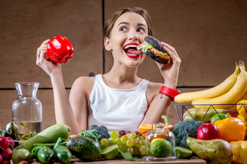 Kobieta przed stołem zastawionym zdrowym jedzeniem