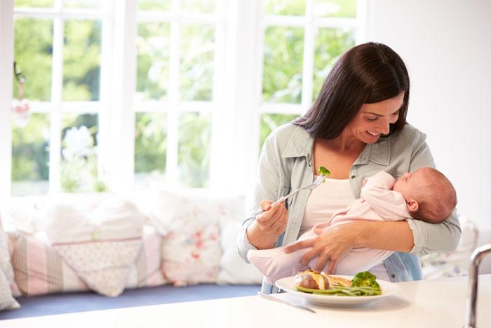 matka z dzieckiem na ręku je sałatkę