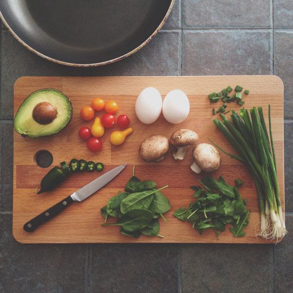 awokado, jajka, warzywa na desce do krojenia