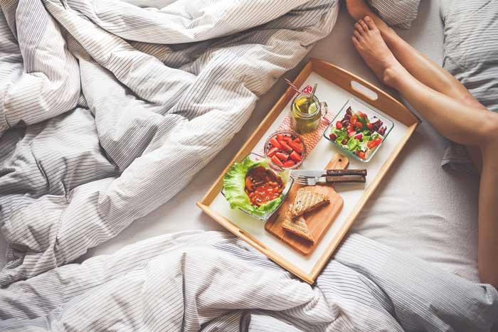 taca z jedzeniem na łóżku, nogi kobiety